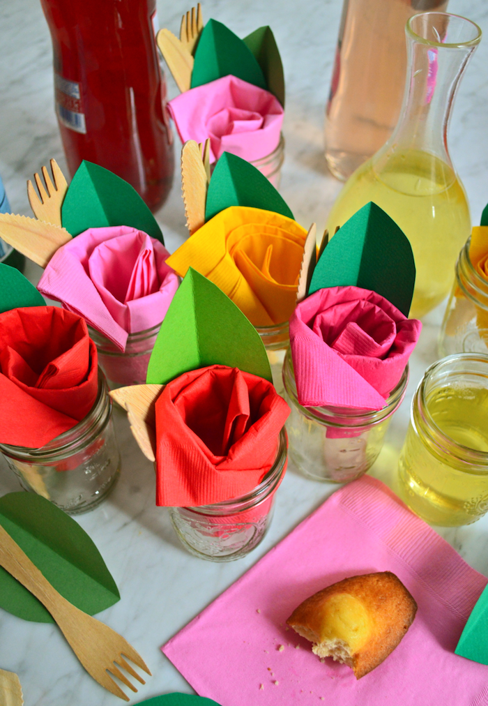 idee deco table anniversaire originale, pliage serviette papier en forme de rose rose, rouge, jaune parée d une feuille en papier