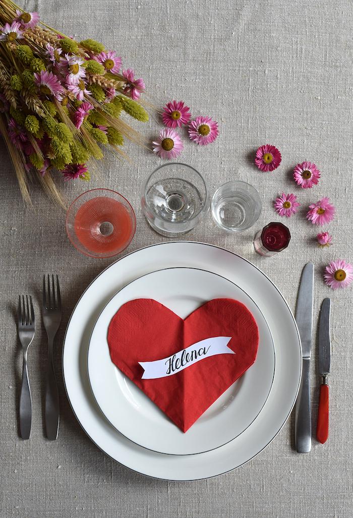 deco table saint valentin originale avec pliage des serviette coeur rouge dans assiette blanche sur nappe grise et deco florale table