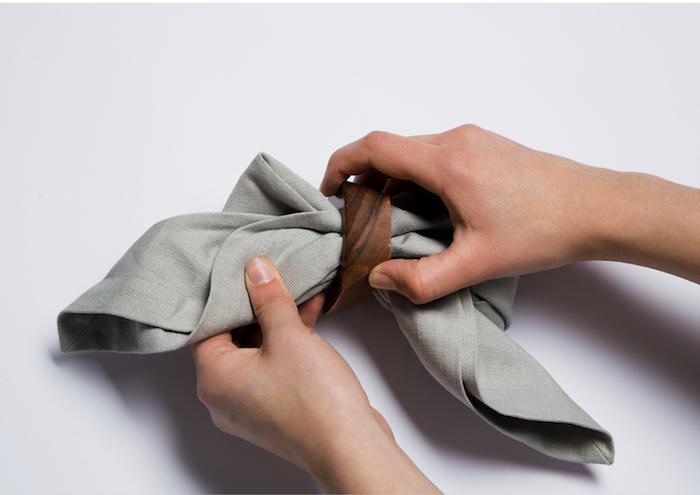 pliage serviette tissu gris en forme de noeud de papillon avec rond de serviette de bois