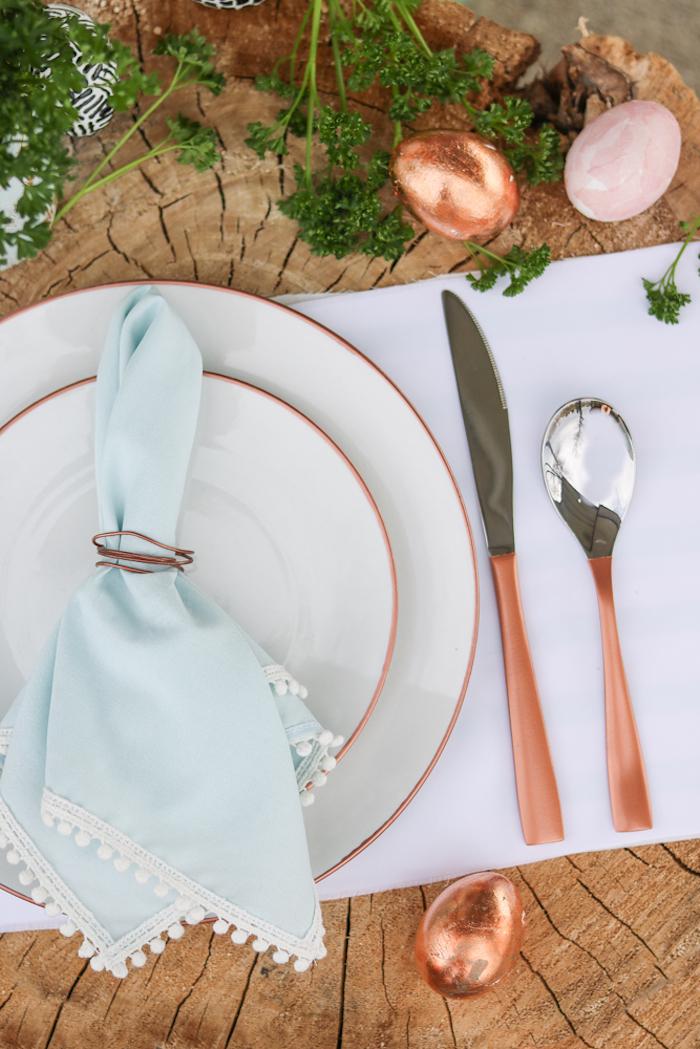 pliage de serviette de table en tissu bleu clair à festons avec rond de serviette cuivre, deco table style champetre chic
