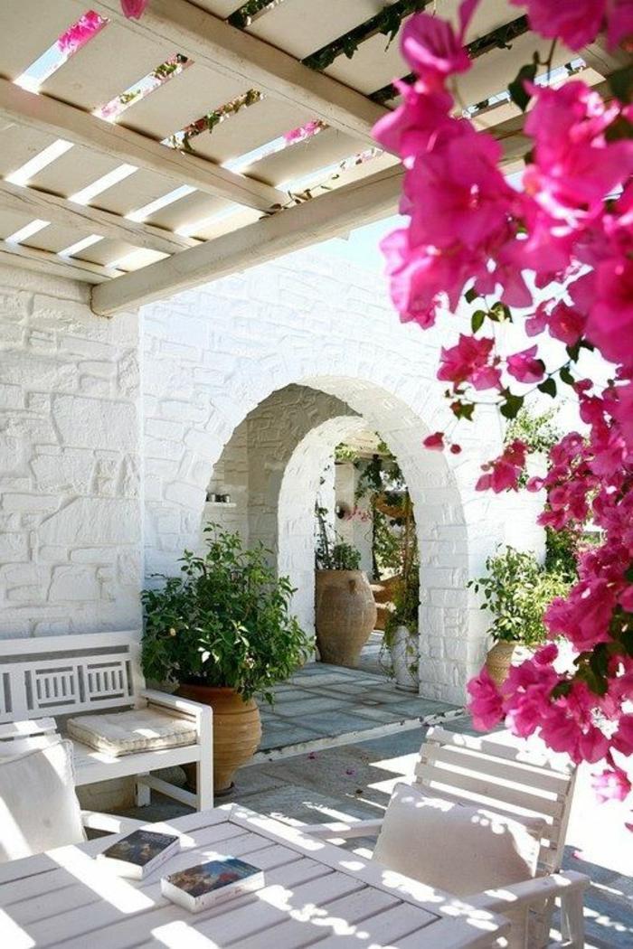 jardin-avec-fleurs-plante-grimpante-maison-de-pierre-blanc-meubles-de-jardin-blancs