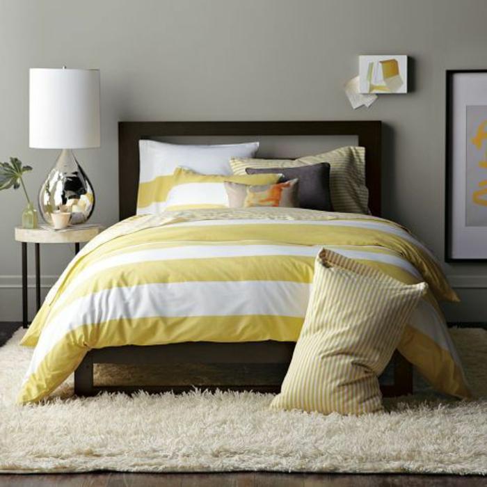 lit-avec-linge-de-lit-coloré-tapis-beige-sol-en-parquette-foncé-mur-gris-peinture