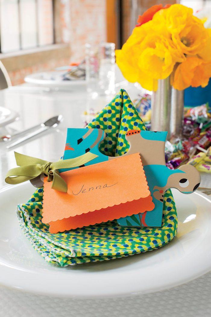 pliage de serviette original en forme de panier vert à fleurs bleu et jaune, marque place doy dans papier orange