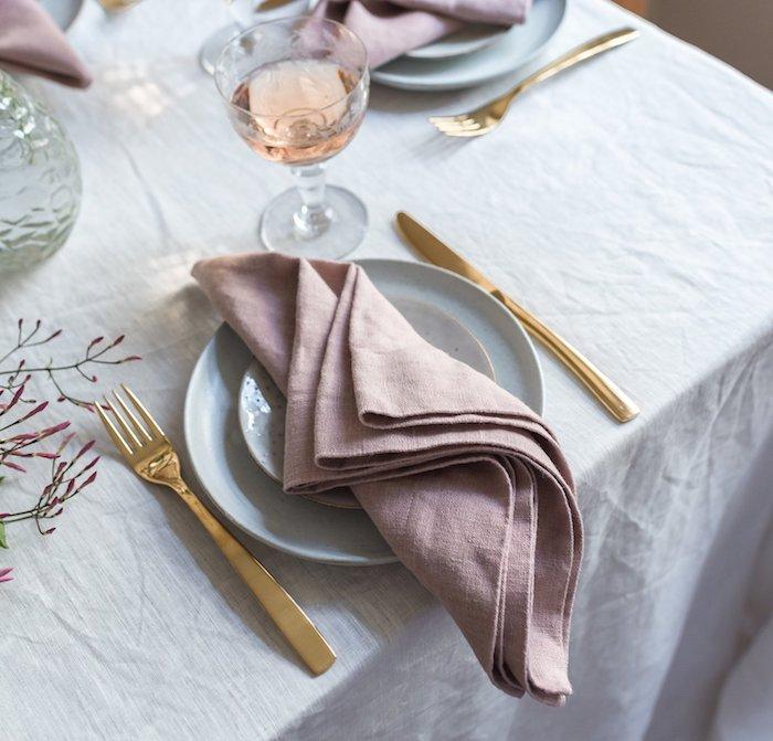 pliage serviette facile rose pale sur nappe blanche, couverts de table or, idee pliage de serviette facile
