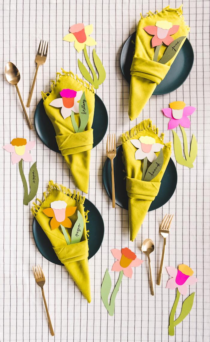 deco table printemps, pliage serviette en triangle forme de carotte avec fleur de papier coloré pour décorer assiette bleu foncé