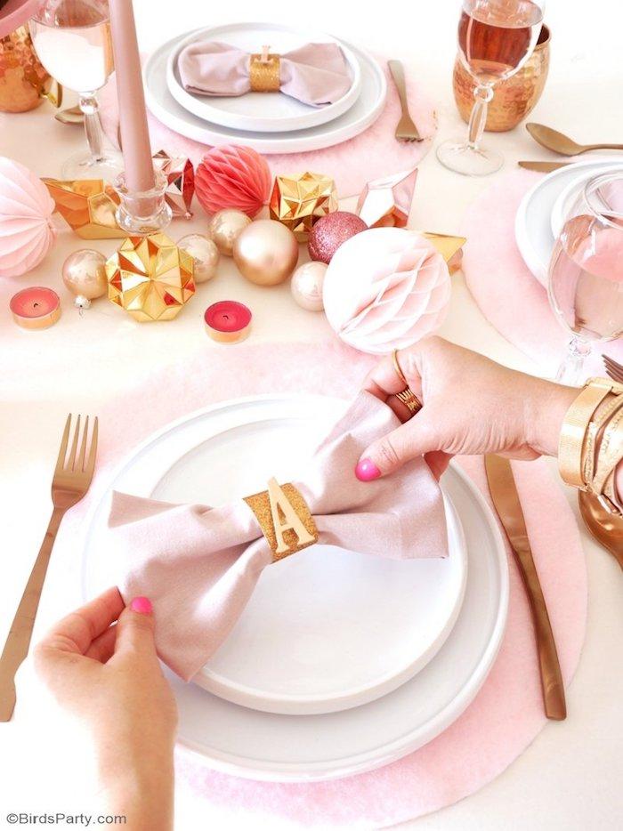 modele pliage serviette simple en noeud de papillon rose clair avec ron serviette pailleté en lettre A, deco table de noel, centre de table en boules de noel
