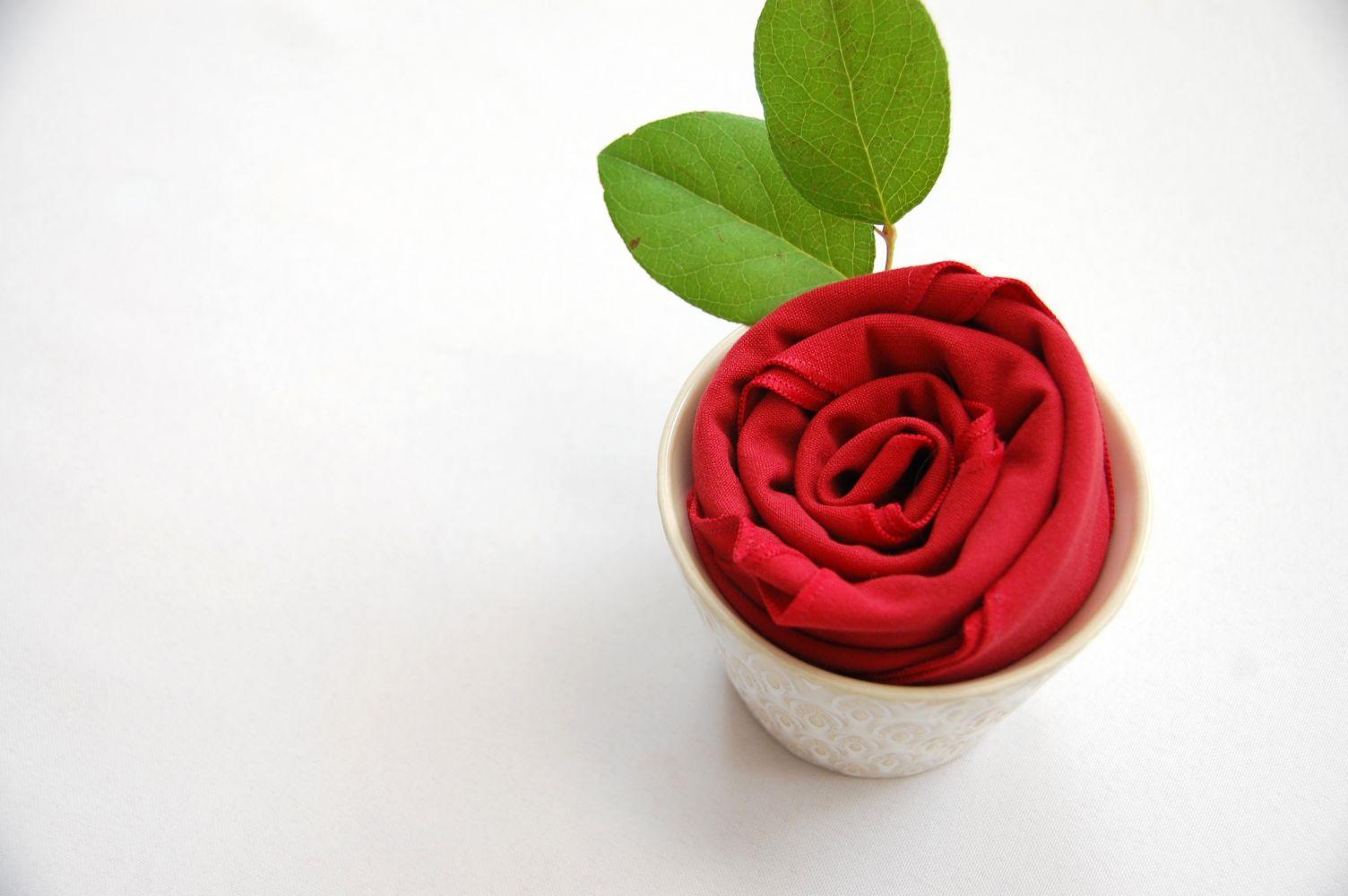 exemple pliage de serviette tissu en forme de rose dans verre avec feuilles vertes naturelles, deco table romantiques