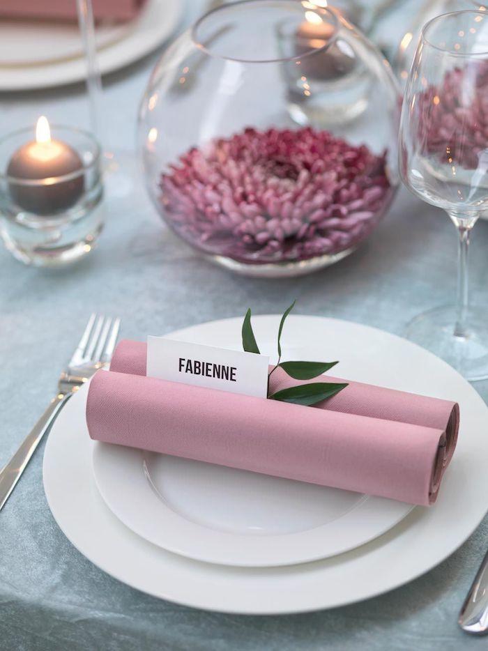 exemple de pliage de serviette simple et beau en rouleau de papier rose avec étiquette porte prénom dans papier blanc, feuille verte decorative
