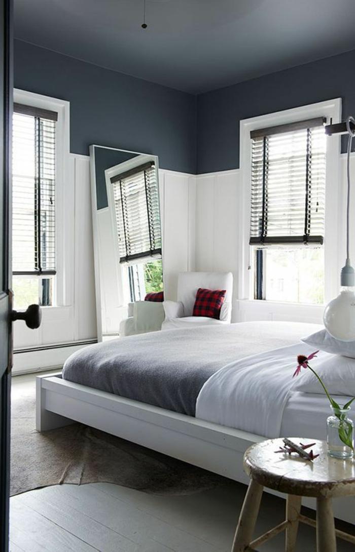 stores-venitiens-dans-la-chambre-à-coucher-plafond-gris-lit-avec-couverture-de-lit-gris-plafond-miroir-dans-la-chambre-à-coucher