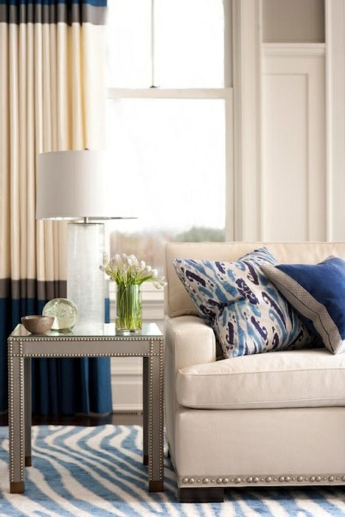 tapis-à-rayures-blanc-bleu-ciel-lampe-de-chevet-blanche-fleurs-sur-la-table-de-chevet-rideaux-beiges