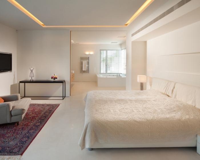 une-jolie-chambre-à-coucher-blanche-avec-tapis-coloré-murs-blancs-plafond-faux