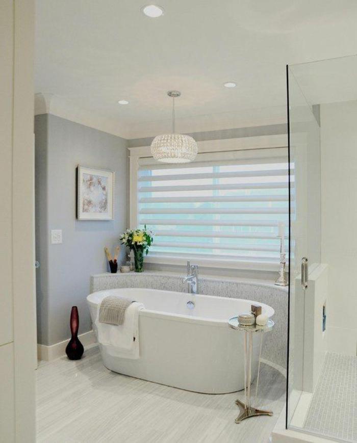 une-jolie-salle-de-bain-avec-store-vénitien-baignoire-blanche-lustre-blanc-cristal-mur-gris