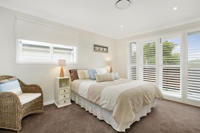 une-vaste-chambre-à-coucher-de-couleur-taupe-moquette-beige-table-de-nuit-en-bois-clair-lampe-de-lecture