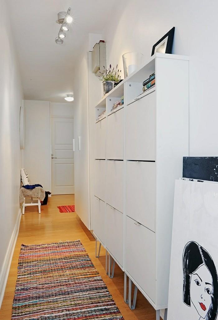1-range-chaussures-dans-le-couloir-avec-sol-en-parquette-clair-et-tapis-coloré-dans-le-couloir