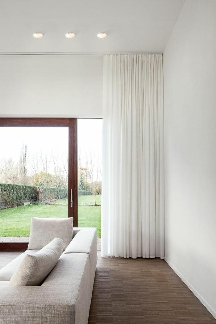 1-un-joli-voilage-blanc-pour-le-salon-avec-fenetres-grandes-canapé-gris-et-un-joli-jardin-avec-pelouse-verte