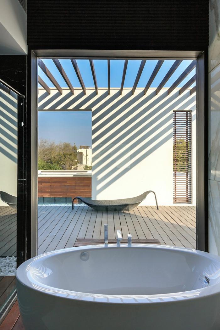 baignoire-ronde-donnant-vers-une-grande-terrasse-en-bois