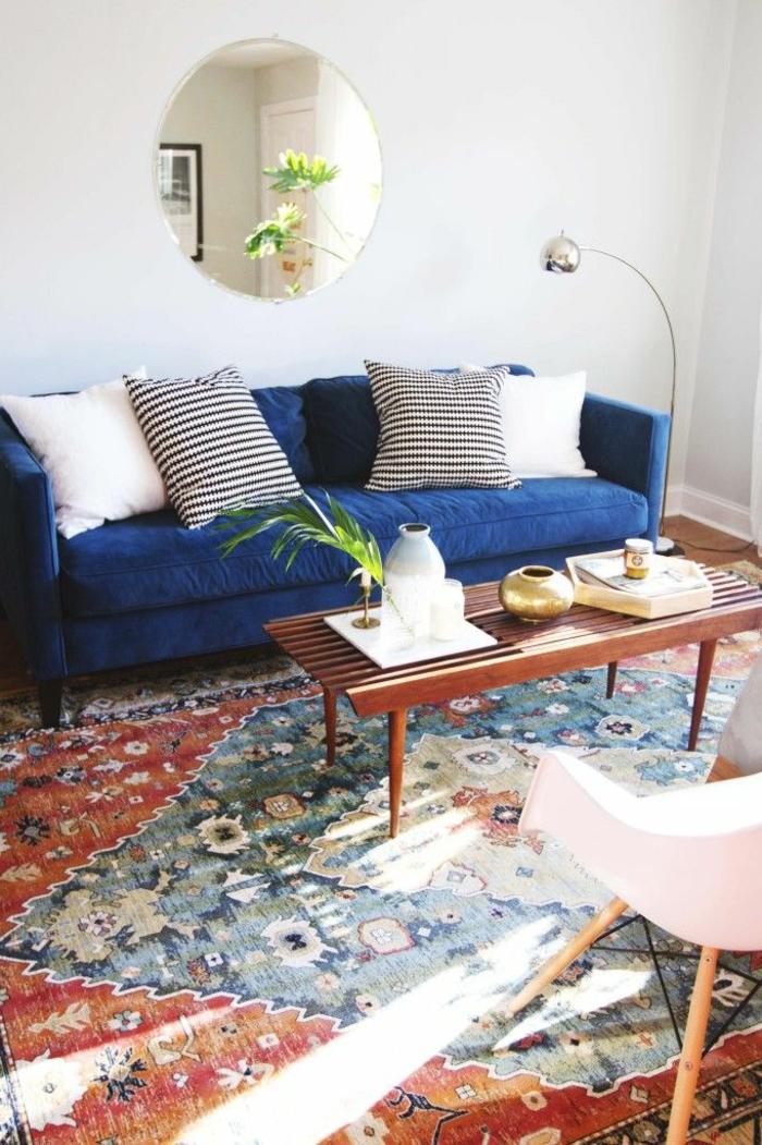 joli-salon-avec-canapé-bleu-foncé-tapis-coloré-dans-la-salle-de-séjour-murs-beiges