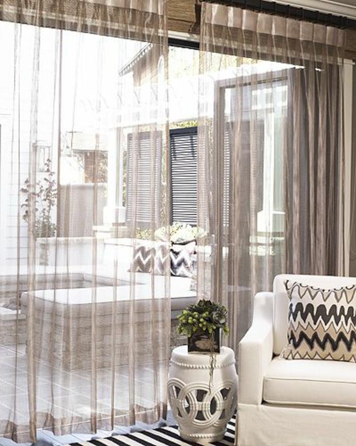 le-rideau-voilage-beige-dans-le-salon-avec-un-fauteuil-blanc-et-fleurs-dans-le-salon