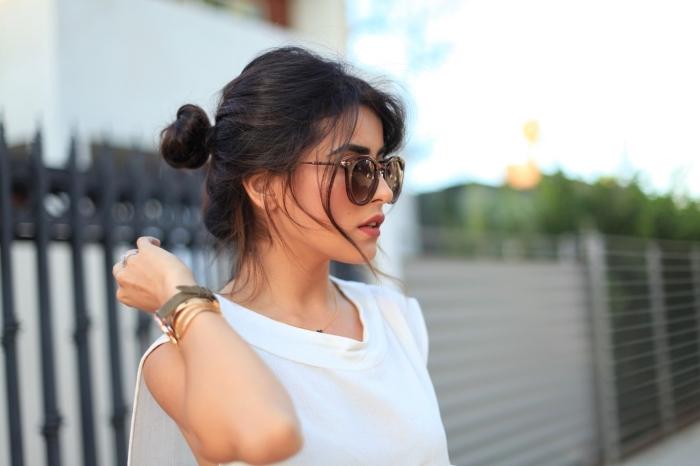 coiffure facile a faire seule, Sazan Handrix aux cheveux mi longs attachés en chignon loose avec mèches tombantes sur visage