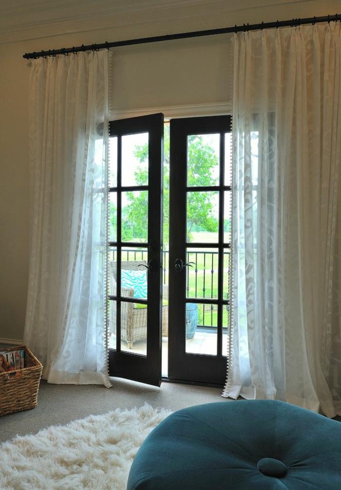 rideau-voilage-blanc-pour-la-porte-de-la-terrasse-dans-la-chambre-à-coucher-avec-moquette-et-chaise-boule-bleue