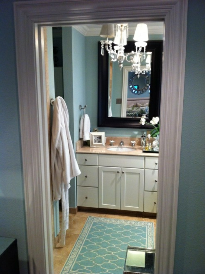 un-joli-tapis-de-salle-de-bain-bleu-avec-lustre-baroque-et-un-commode-en-bois-blanc
