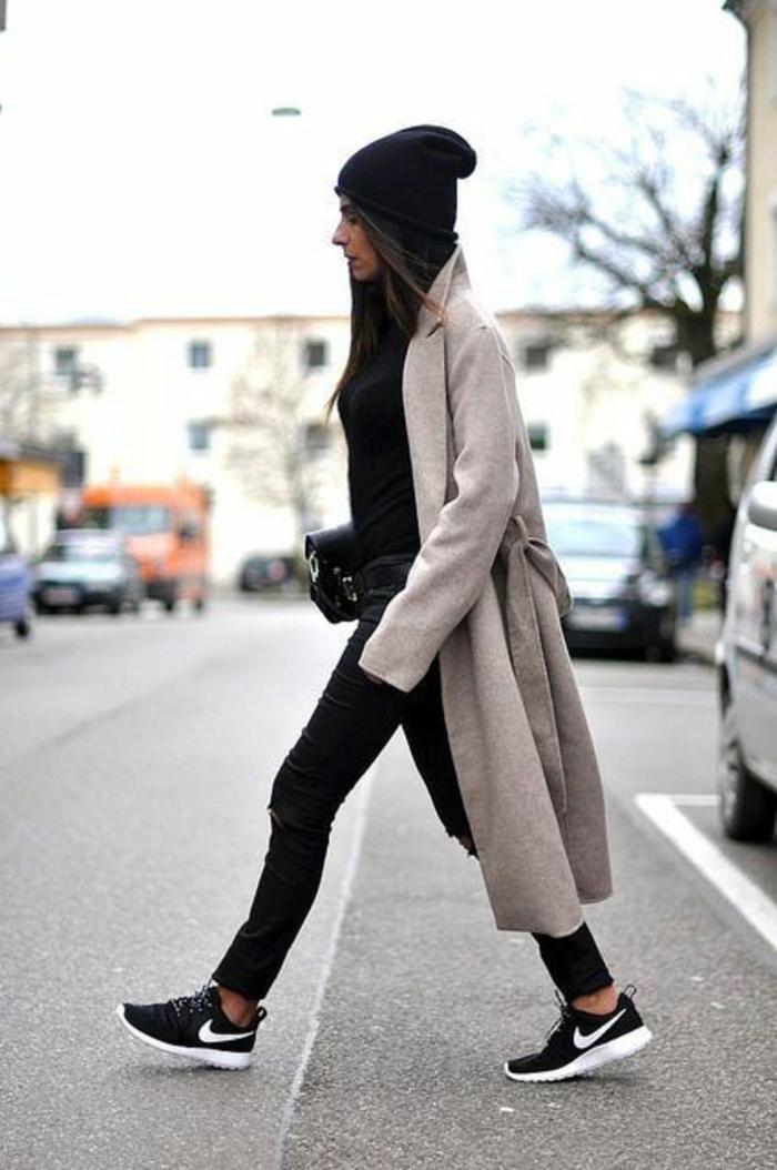 une-femme-marche-sur-la-rue-avec-manteau-long-femme-beige-outfit-noir-sneakers-noir-blanc