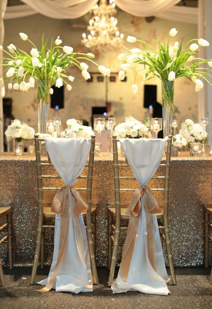 ... chaises de mariage avec un ruban élégant et fleurs sur la table de