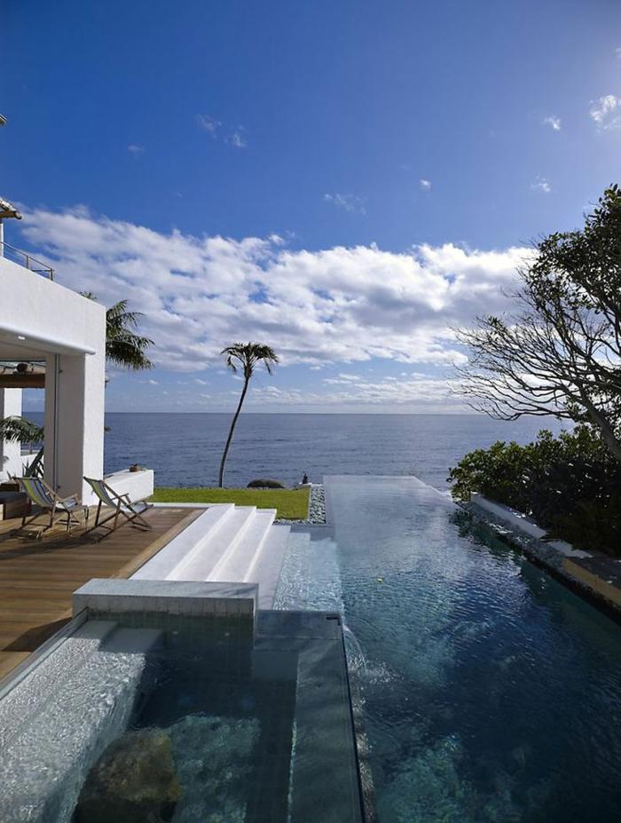 une-jolie-jardin-avec-piscine-d-extérieur-moderne-infini-pres-de-la-mer-une-maison-de-luxe