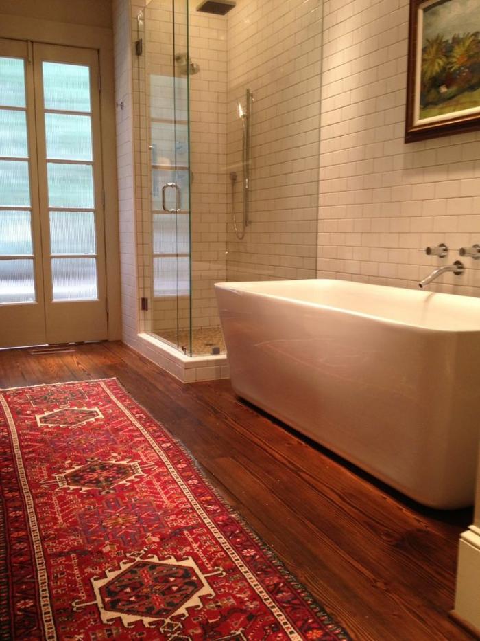 une-jolie-salle-de-bain-avec-carrelage-blanc-et-sol-en-parquette-en-bois-foncé
