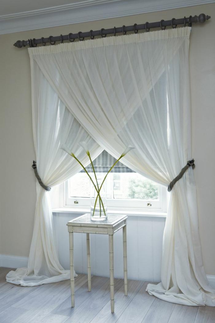 voilage-blanc-pour-la-chambre-à-coucher-avec-un-meuble-blanc-et-fleurs-pres-de-la-fenetre