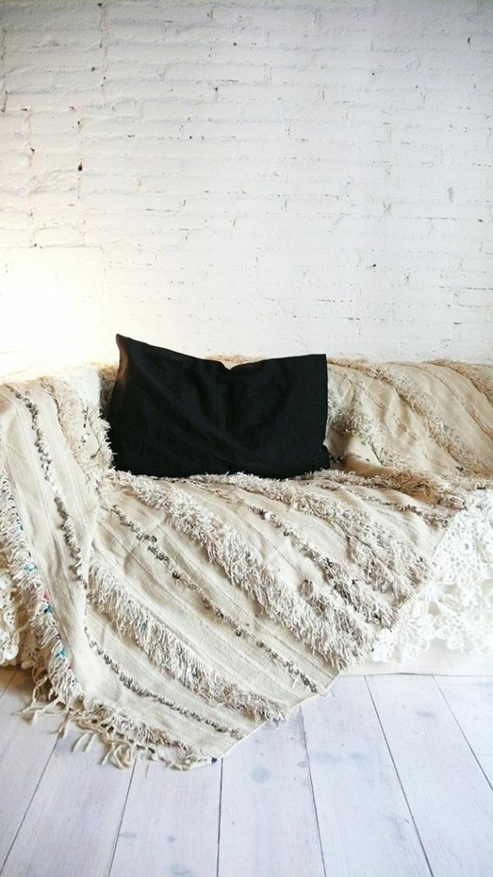 1-protege-canape-avec-un-plaid-pour-canapé-et-coussin-noir-mur-blanc-en-briques-bancs