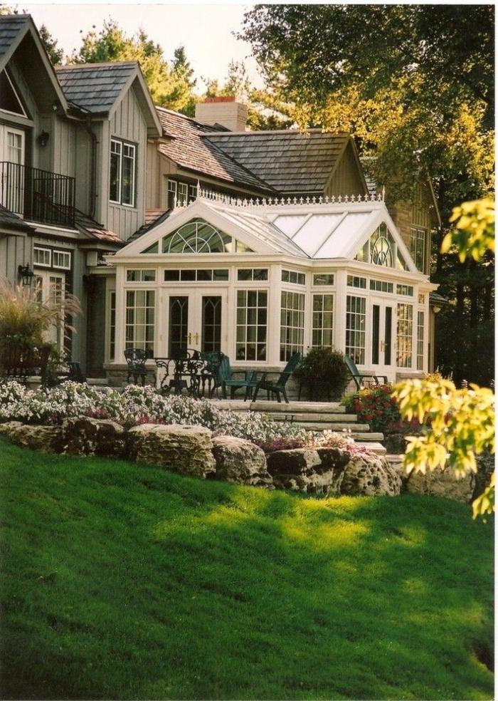 1-vérandas-en-kit-dans-le-jardin-avec-pelouse-verte-devant-la-maison-avec-mur-en-verre-et-plafond-sous-combles