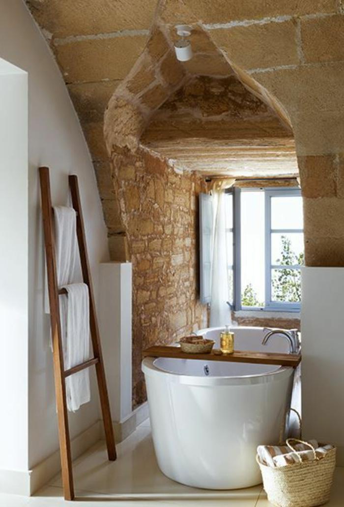 aménager-une-petite-salle-de-bain-mur-de-pierres-beiges-pour-la-salle-de-bain-avec-baignoire-blanche