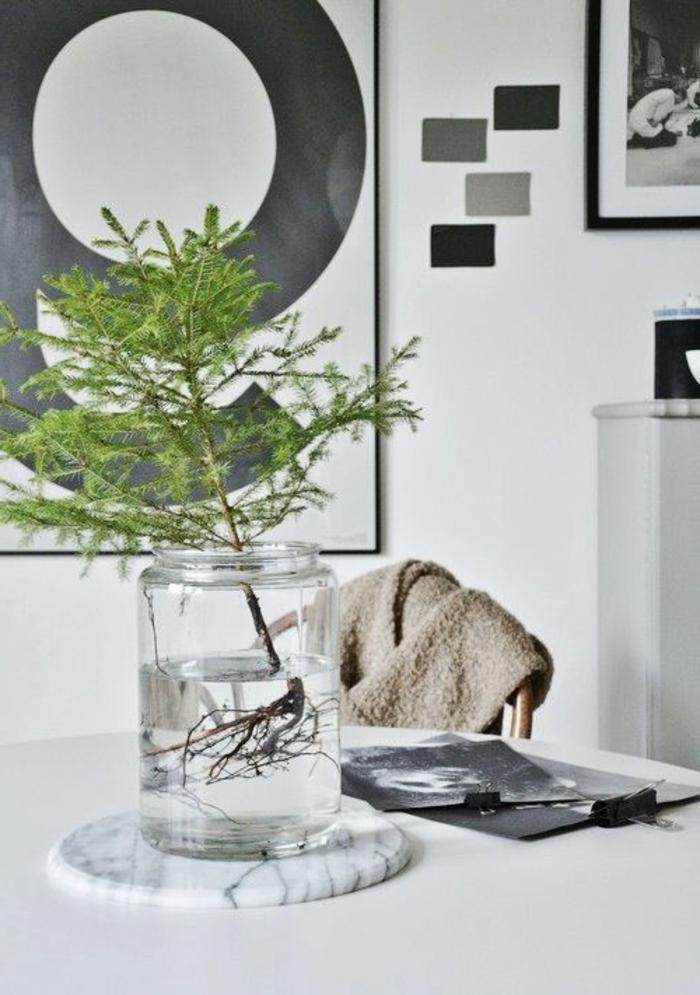 branche-de-sapin-sur-la-table-dans-la-salle-de-séjour-blanche-murs-blancs-table-blanche