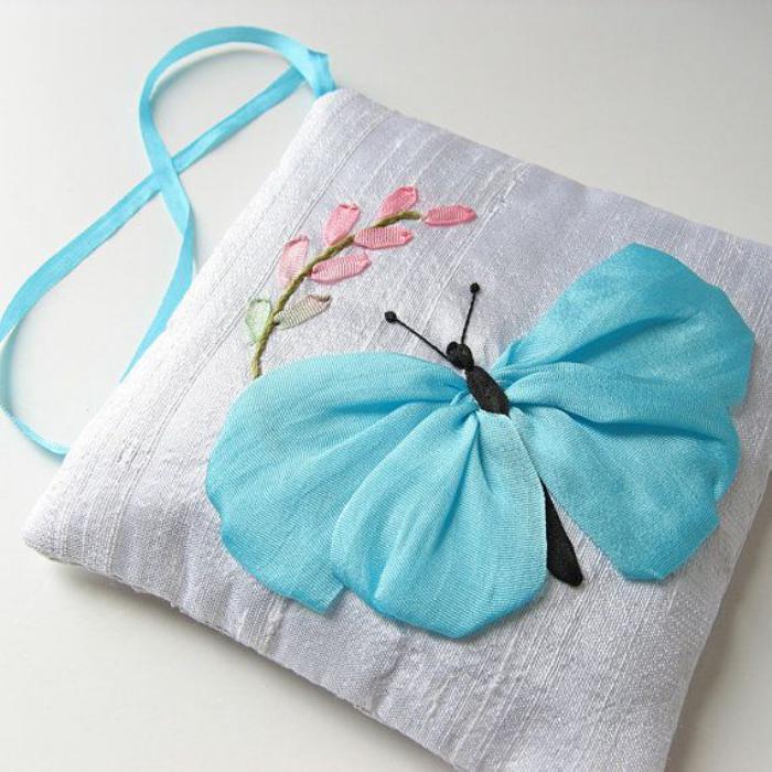 broderie-au-ruban-papillon-bleu-sur-un-coussin-gris