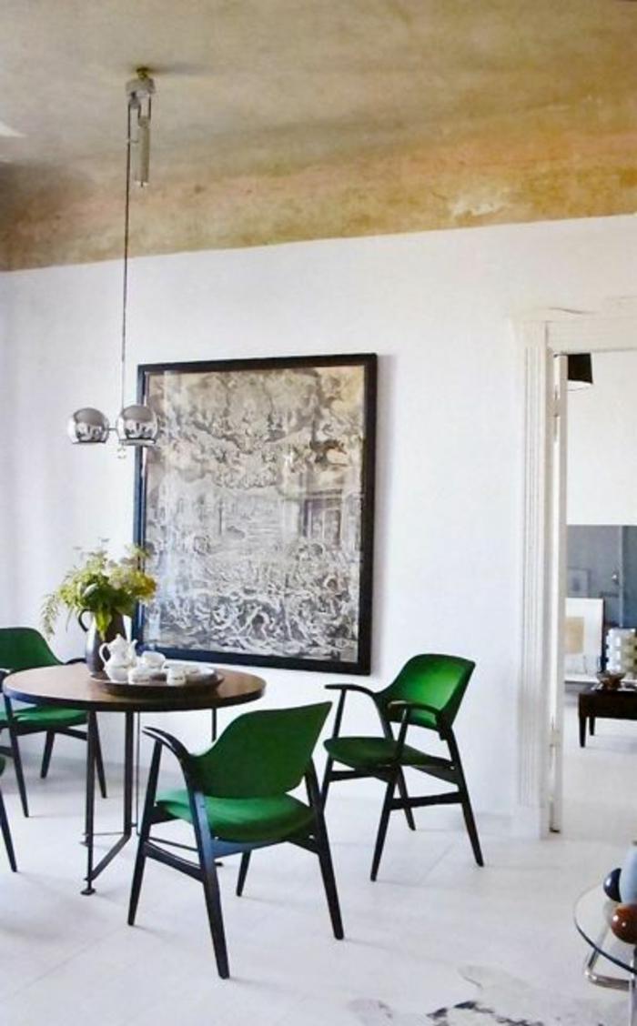 chaises-vertes-et-une-jolie-table-ronde-en-bois-mur-blanc-et-plafond-beige-murs-blancs