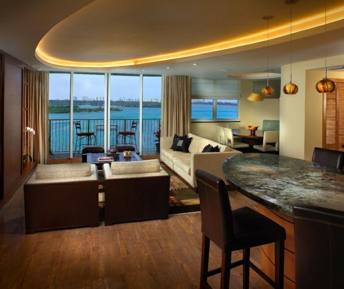 comiche-eclairage-indirect-dans-le-salon-contemporain-sol-en-parquet-foncé-et-balcon-avec-vue-vers-l-ocean