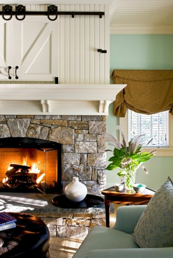 decoration-murale-en-pierres-gris-salon-avec-canape-bleu-et-fleurs-verts-mur-en-pierre-de-parement-intérieur