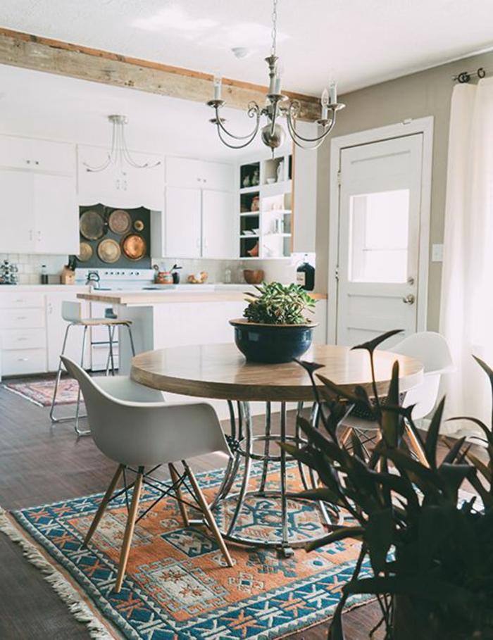 idee-deco-sejour-tapis-colore-et-table-ronde-en-bois-fleurs-sur-la-table-et-un-lustre-baroque