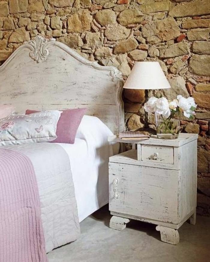 jolie-chambre-a-coucher-avec-mur-imitation-pierre-et-fleurs-blanches-sur-le-meuble-d-appoint