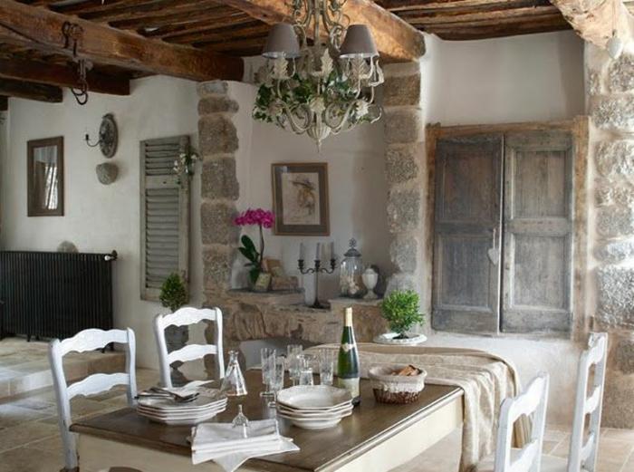 jolie-cuisine-avec-mur-en-pierre-de-parement-intérieur-table-en-bois-et-chaises-blanches