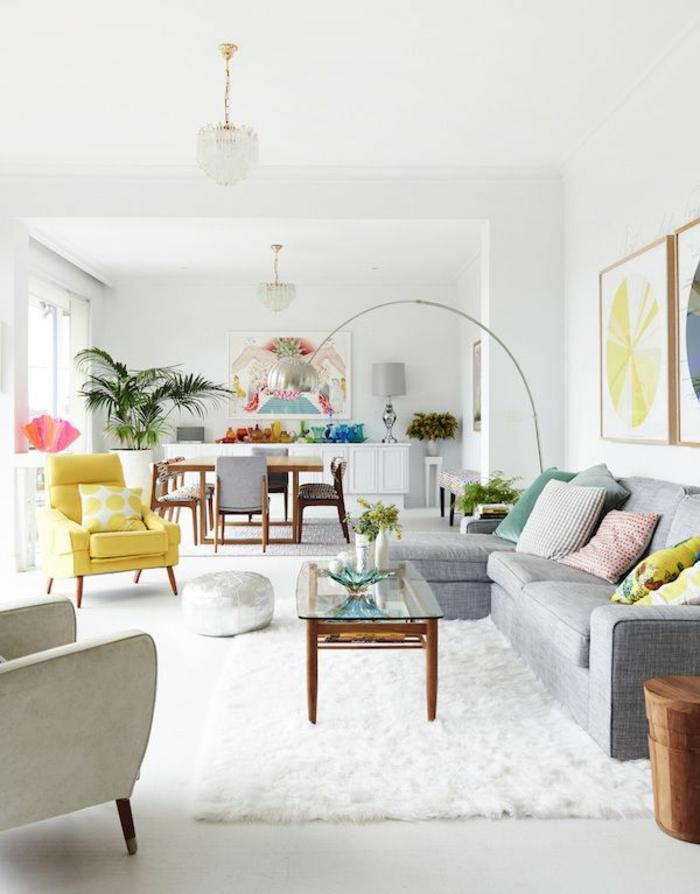 lampe-de-salon-sur-pied-et-tapis-blanc-et-canapé-gris-avec-coussins-colorés-et-peintures-murales