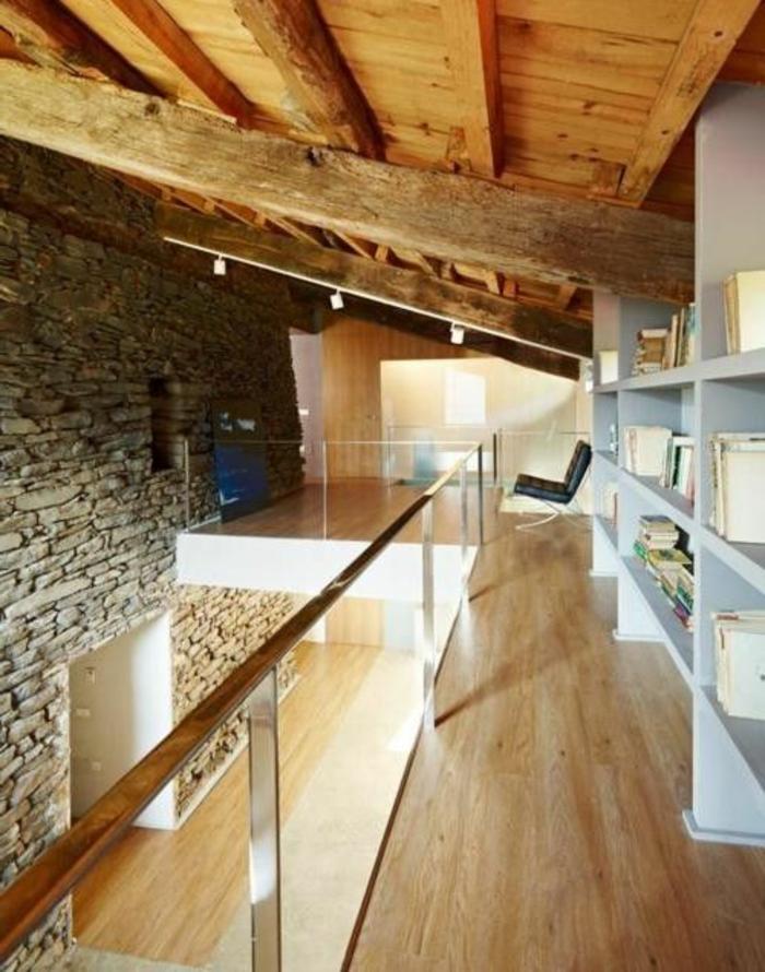 mur-en-pierre-de-parement-intérieur-sol-en-parquet-clair-et-meubles-gris-plafond-sous-pente-en-bois-clair