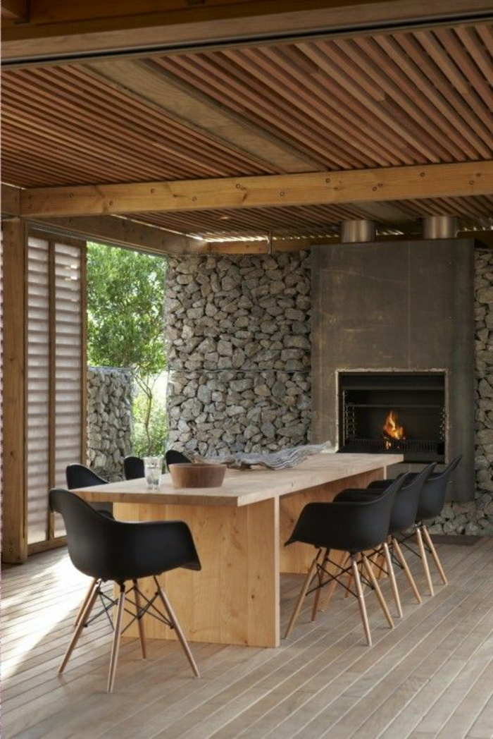 salle-de-sejour-avec-mur-en-pierre-de-parement-intérieur-gris-et-table-en-bois-clair