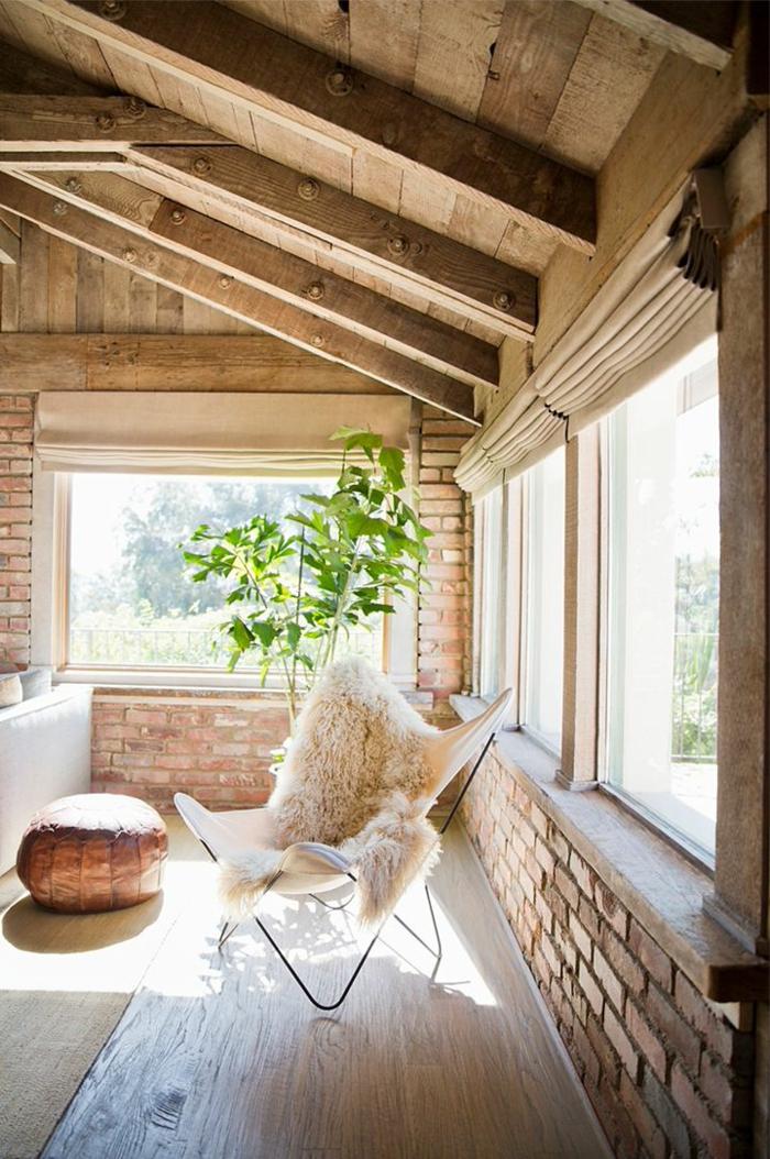 salon-plafond-avec-poutre-bois-massif-et-plafond-sous-pente-mur-de-briques-rouges