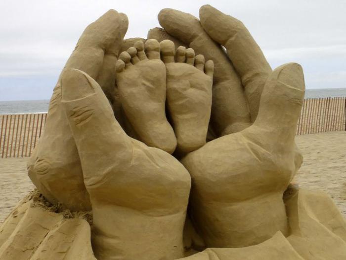 sculpture-de-sable-des-mains-qui-tiennent-des-pieds