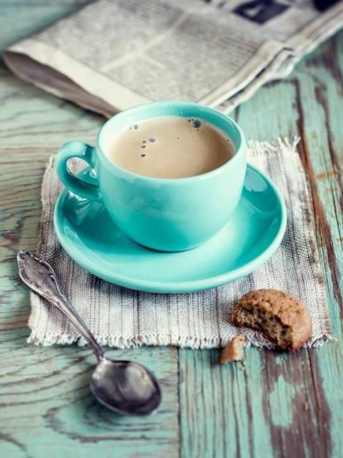 1-tasse-à-café-nespresso-bleu-clair-avec-biscuit-une-table-en-bois-massif-et-tasses-à-café-bodum