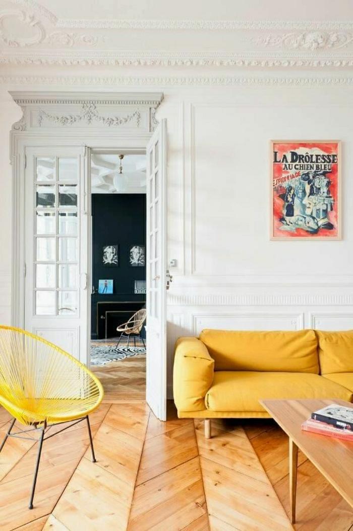 2-moulures-decoratives-avec-corniche-plafond-canape-jaune-en-cuir-et-chaise-en-rotin-jaune-sol-en-parquet-clair