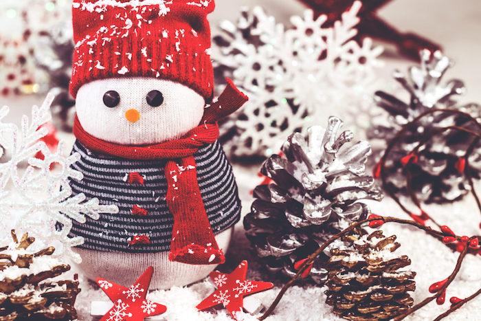 bonhomme de neige en chaussette blanche avec pull et écharpe recyclés et bonnet rouge tricot, activité manuelle noel et deco