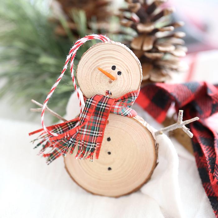 activité manuelle noel, bonhomme de neige en rondins de bois assemblés avec une écharpe et suspension fil rouge et blanc